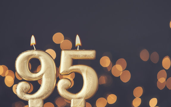 Gold number 95 celebration candle against blurred light background