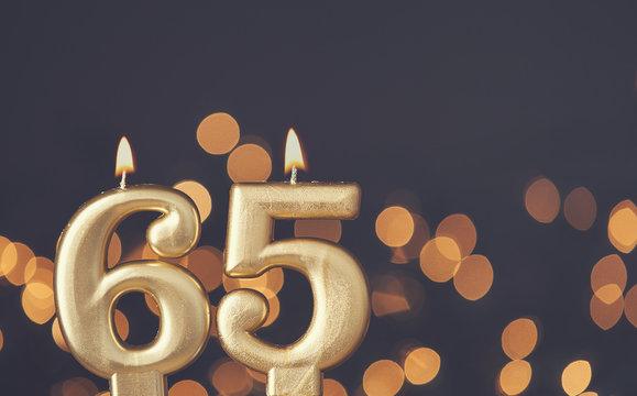 Gold number 65 celebration candle against blurred light background