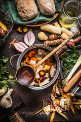 Cooking pot with wooden spoon and vegetables on rustic kitchen table background. Homemade healthy food and eating or vegetarian concept