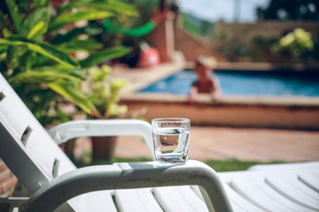 Glass of water with drops by pool side in tropical beach resort