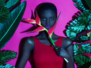 Portrait of a dark-skinned girl with an exotic flower