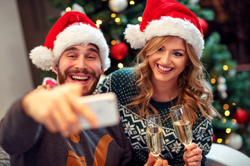 love couple having fun and take pictures of Christmas on mobile phone .
