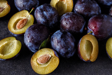 close up of plums and plums slices on dark background .