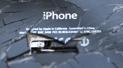 A broken iPhone is seen on a table in this illustration picture