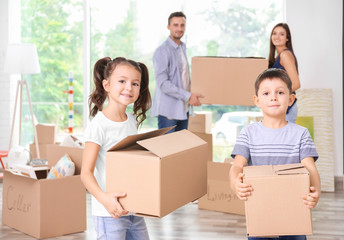 Cute little children with moving boxes in room at new home