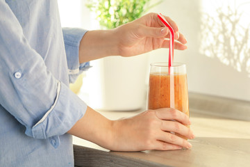 Woman holding glass with smoothie indoors