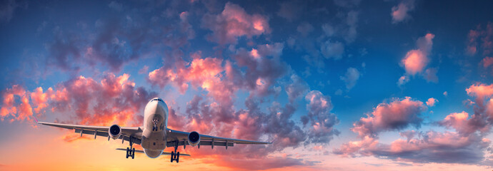 Poster Avion à Moteur Airplane and beautiful sky. Landscape with passenger airplane is flying in the blue sky with red, purple and orange clouds at sunrise. Travel. Passenger airliner. Commercial aircraft. Private jet