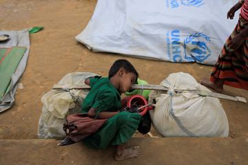 A Rohingya refugee girl who crossed the border from Myanmar this week sleeps beside his family belongings as he take shelter at a school in  Kotupalang refugee camp near Cox's Bazar,