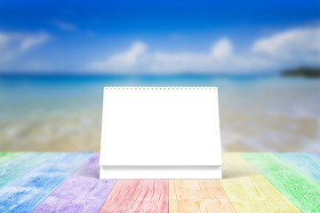 Blank desk calendar on wooden desk. Front view. Mockup template to replace your design.