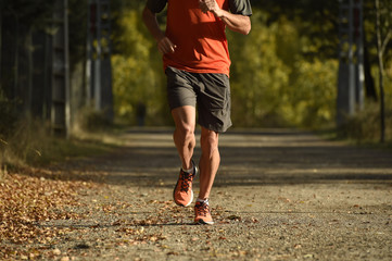 sport man with ripped athletic and muscular legs running off road in jogging training workout at countryside in Autumn background