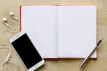 blank notebook with pen on wood table And a wrist watch headset Modern phone Text input area