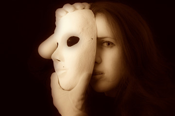 brunette girl is holding a theater mask in front of their face