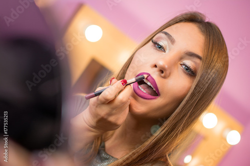 Beautiful young woman applying makeup putting on lip liner and