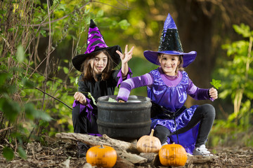 Girls in a costume of witches making magic potion