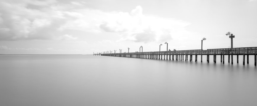 Long exposure wooden fishing pier stretching out over Galveston Bay in La Porte, Texas, USA. Foot pier for saltwater fishing with motion blurred people, recreation concept. Panorama nature seascape
