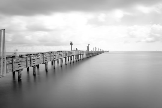 Long exposure wooden fishing pier stretching out over Galveston Bay in La Porte, Texas, USA. Foot pier for saltwater fishing with motion blurred people, recreation concept. Nature seascape background