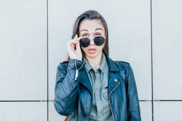 Bright portrait of charming fashion hipster woman in sunglasses and black leather jacket with surprise emotions posing over beige wall.
