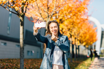 Pretty hipster girl in jeans coat trench taking selfie, smiling and showing sign small heart by fingers in sunny autumn day. Travel, tourism, lifestyle and people concept.