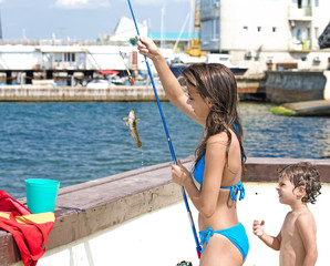 Portrait of happy young girl with her little brother looking at fish on hook in hands outdoors