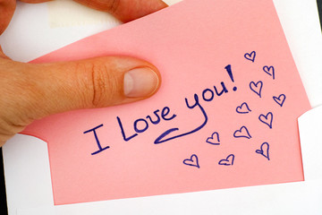 Woman hand taking out letter with text I Love You! from envelope.
