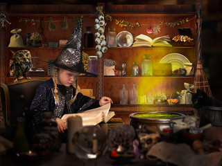 The wizard of room. Little girl in witch hat reads a big book of spells. Many mystical items. The concept of magic, Halloween