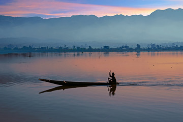 Lonely fisherman fishing at sunrise on a lake in Myanmar