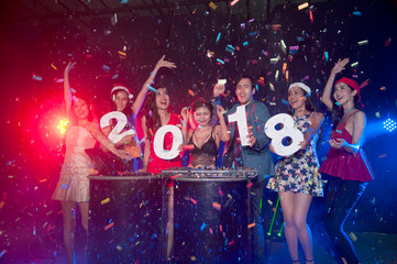 Group of people dancing at night club with santa hat christmas holidays party friendship relaxing celebrating new year 2018..