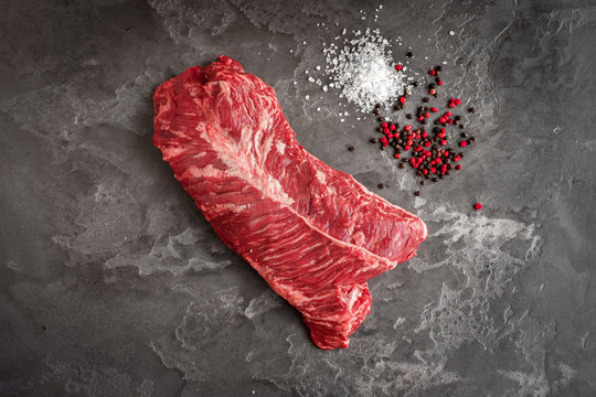 Hanging Tender steak on a stone background with salt and pepper - onglet steak
