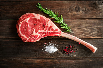 Printed roller blinds Steakhouse raw Tomahawk steak on wooden background with spices for grilling