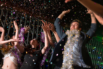 Young people dancing and showered with confetti on a club party on Friday night