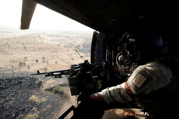 A French soldier from the 5th combat helicopter regiment mans a machine gun of a Sud-Aviation Puma military helicopter in the region of Gao