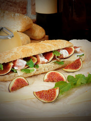 Sandwich with hamon, figs, arugula and Parmesan cheese. Baked products, a bottle of wine and ingredients in the background