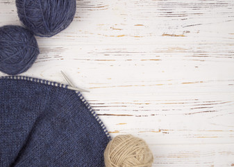 ball of wool with knitting needles and knitting on wooden white background