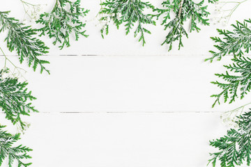 Christmas frame made of thuja branches and gypsophila flowers on white wooden background. Christmas, winter, new year concept. Flat lay, top view, copy space