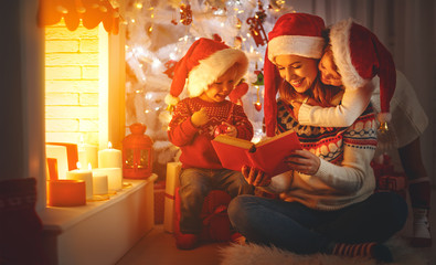 family mother and children read a book at christmas near   fireplace at home