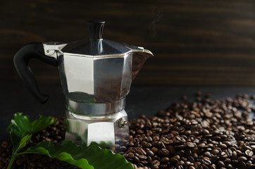 Italian coffee maker and coffee beans with leaves on brown background