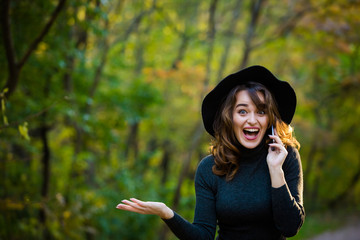 Portrait of a glamorous young lady in a black hat. Autumn Park. Women's emotions.