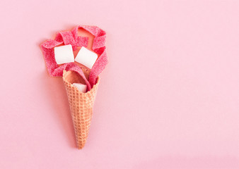 Creative minimal still life on pastel pink colored background. Waffle cone with marshmallows, and red marmalade stripes. Copy space for text