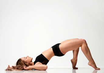 Beautiful caucasian female athlete stretching on a floor