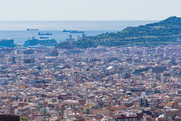 Panoramic view of Barcelona city from park Guell highest hill. Daysun lights out all the city, quarters, famous Sagrada Familia, Mediterranean Sea and endless sky.