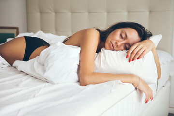 Beautiful tired young woman is sleeping in the bed  in her bedroom at home in the morning. Woman is feeling drowsy after wake up too early in morning, sleepless night.
