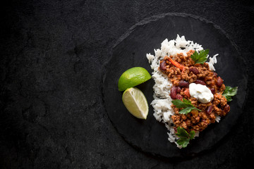Sliced lamb in tomato sauce and rice on dark background with blank space