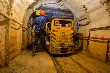 Miner with electrical locomotive underground ore mine shaft tunnel