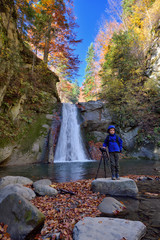 Happy kid near photo camera on tripod with a waterfall in background in autumn