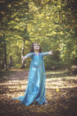 Happy girl in blue dress playing with leaves in the woods,selective focus