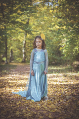 Little girl in blue dress posing in the woods,selective focus