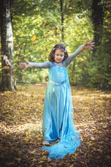 Little girl playing with leaves in the wood,selective focus
