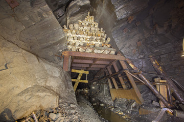 Massive wooden timbering in the underground ore mine shaft tunnel