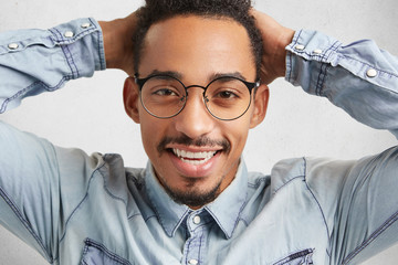 Happy hipster guy in big round spectacles feels relaxed after passinng session, keeps hands on head, smiles happily, enjoys freedom and pleasant atmosphere. Joyful male enterpreneur rejoice success