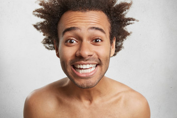 Happy mixed race man smiles happily as recieves pleasant comments from clients, demonstrates white perfect teeth, isolated over white background. Naked young African man rejoice successful day